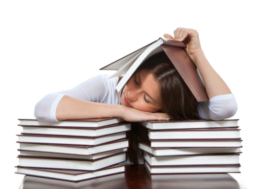 young girl student lying on the table tired sleeping books